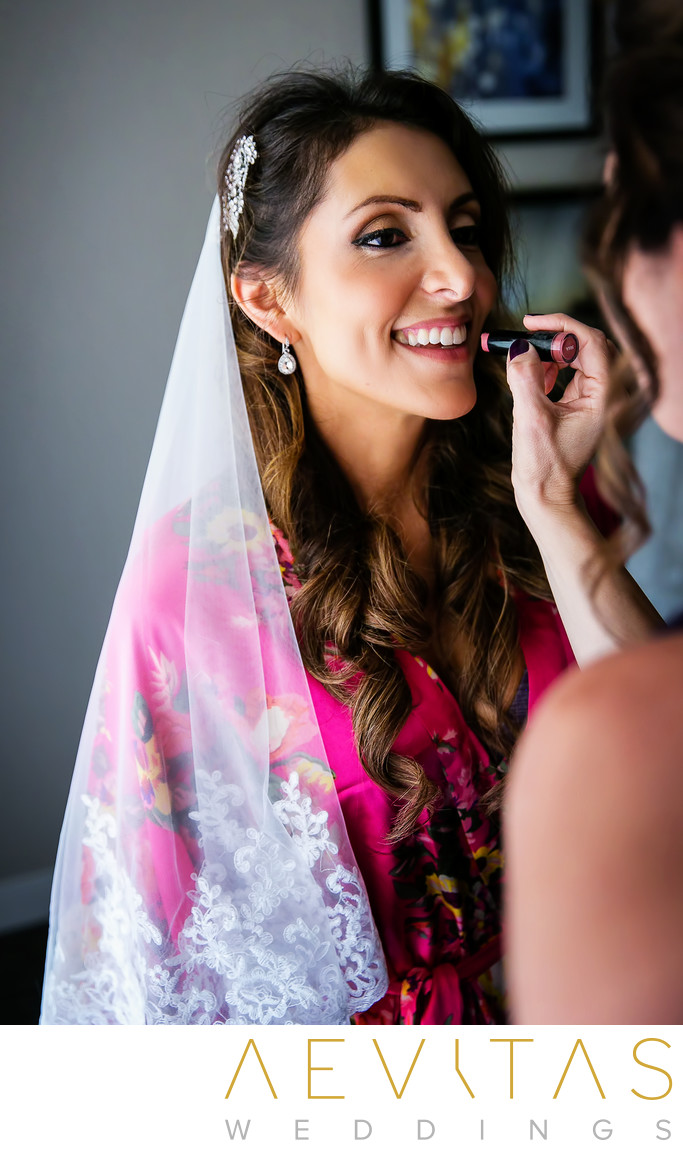 Bride with veil having lipstick applied in hotel suite
