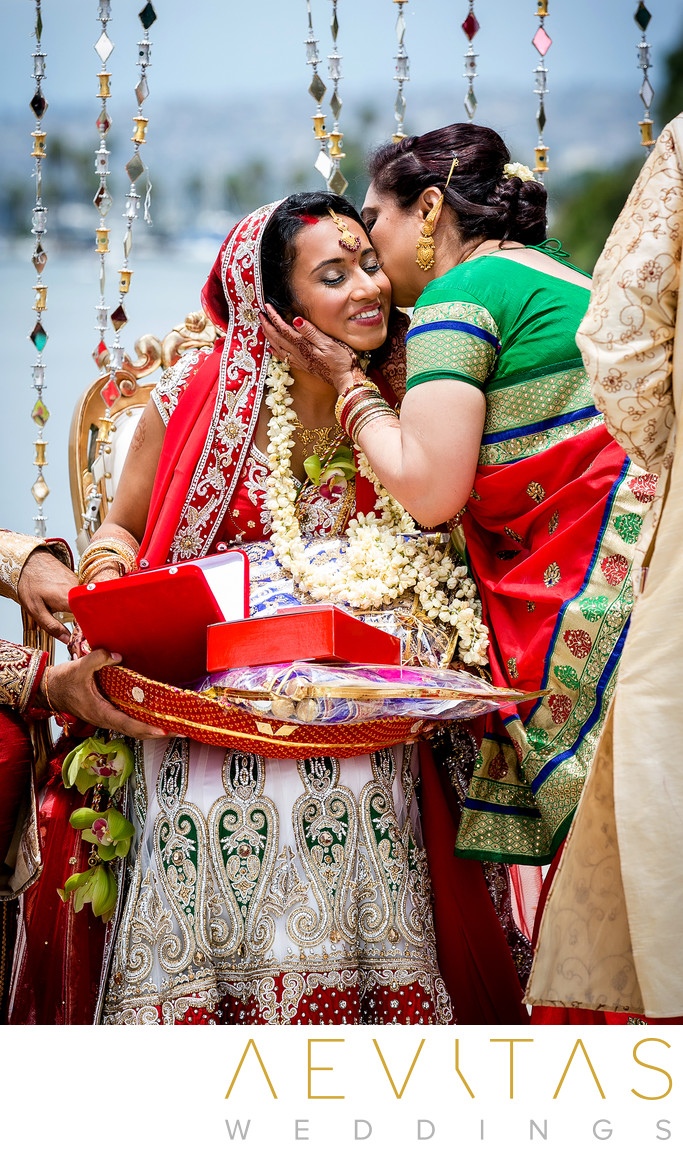 Mother kisses bride during Indian beach wedding