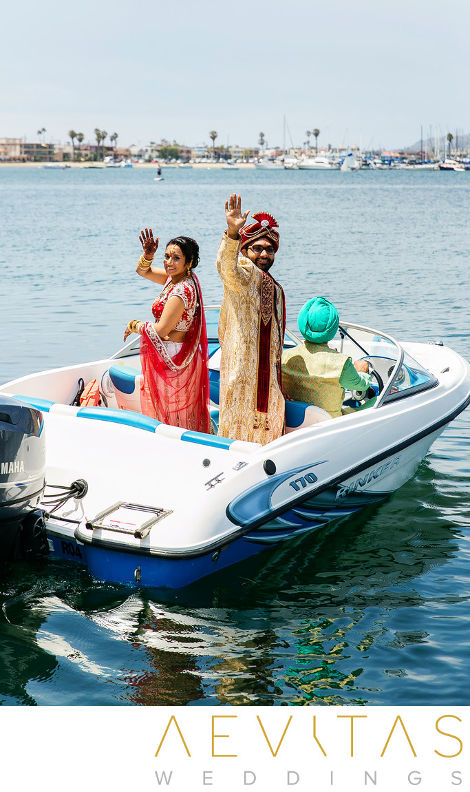 Bride and groom wave on speedboat in San Diego