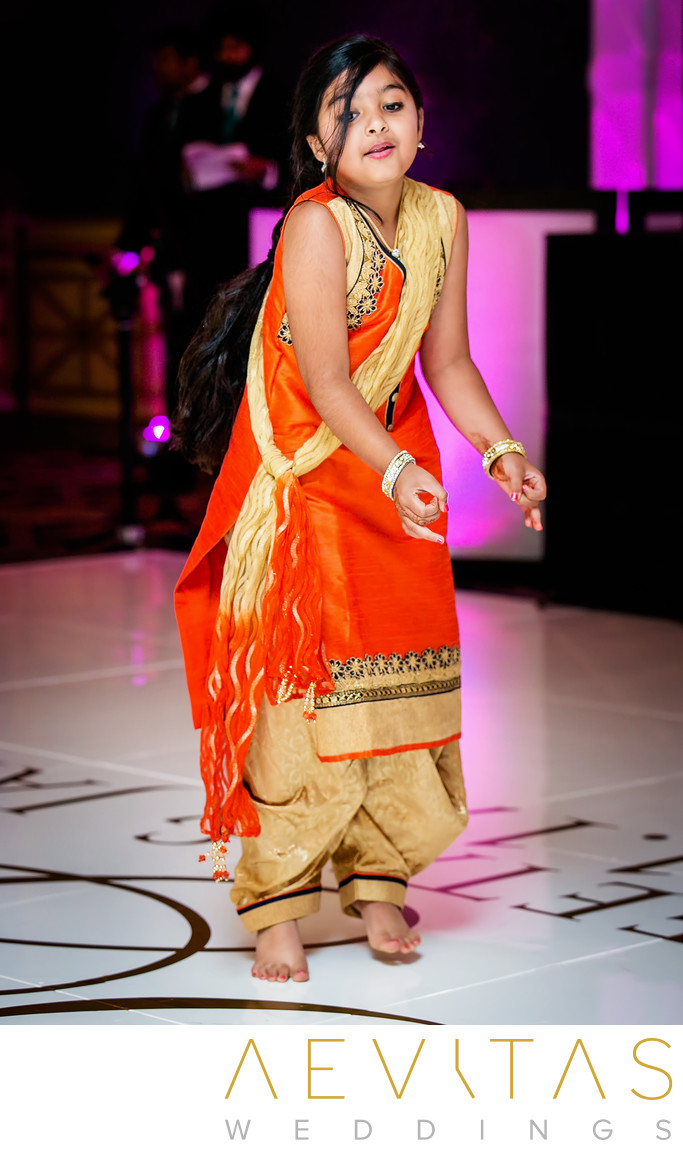 Young wedding guest dancing at Indian reception