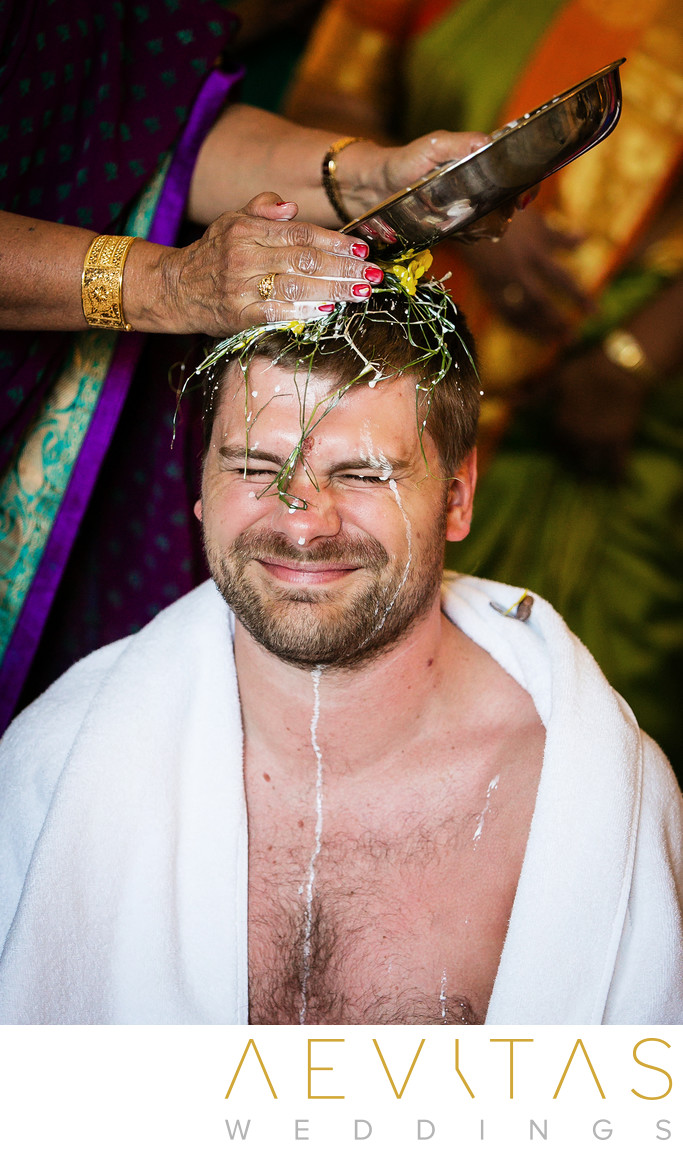 Pouring water on groom's head at Indian wedding