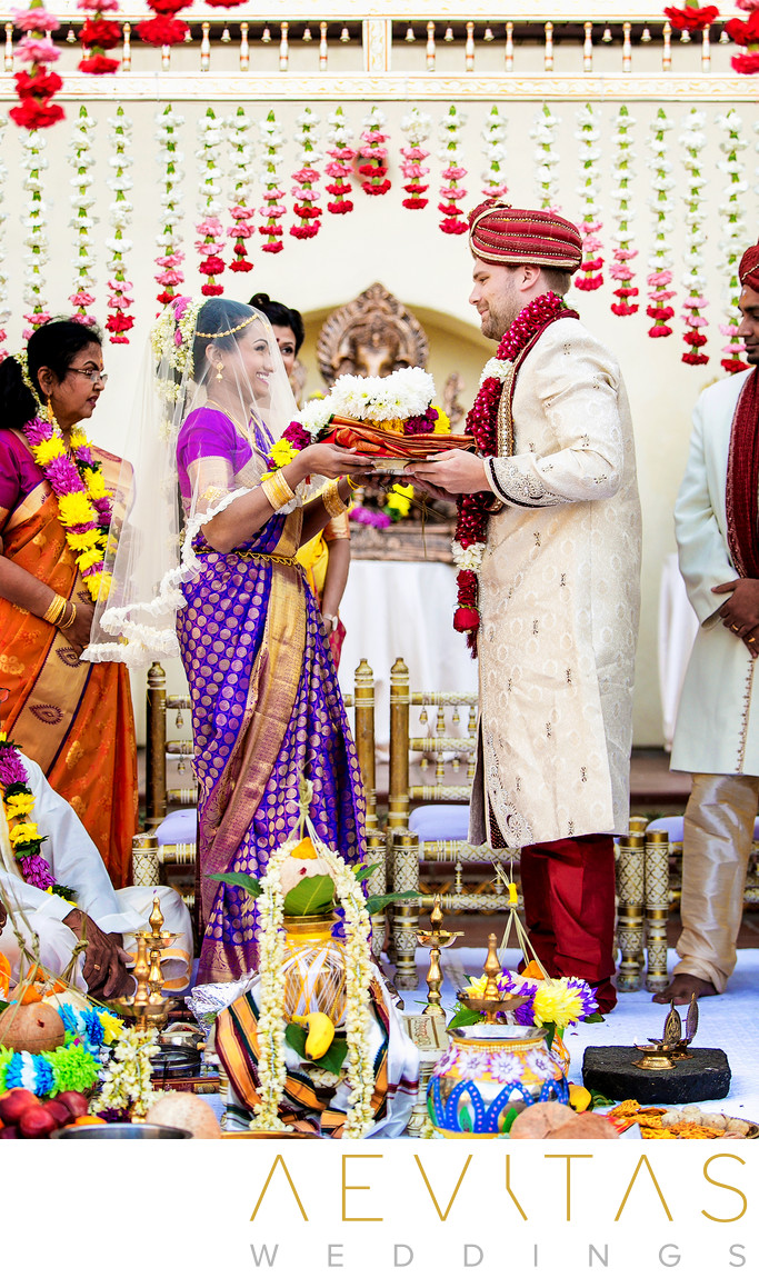 Bride and groom carry flower garlands at Hindu wedding