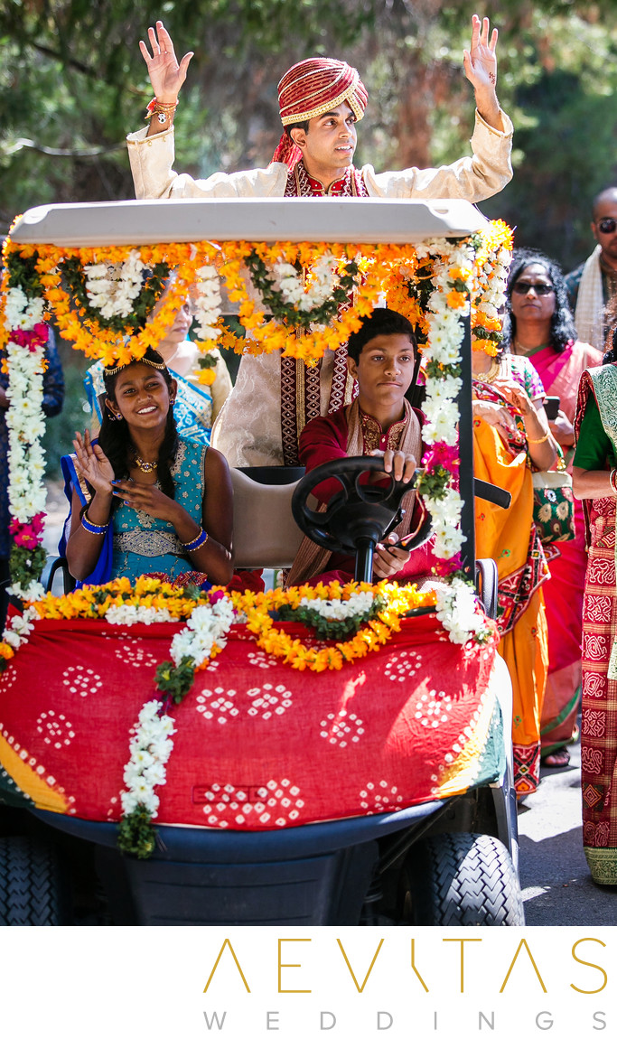 Groom standing in decorated golf cart at Indian wedding