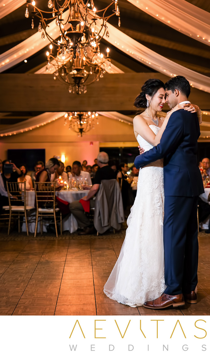 Couple first dance with chandeliers at Pomona wedding
