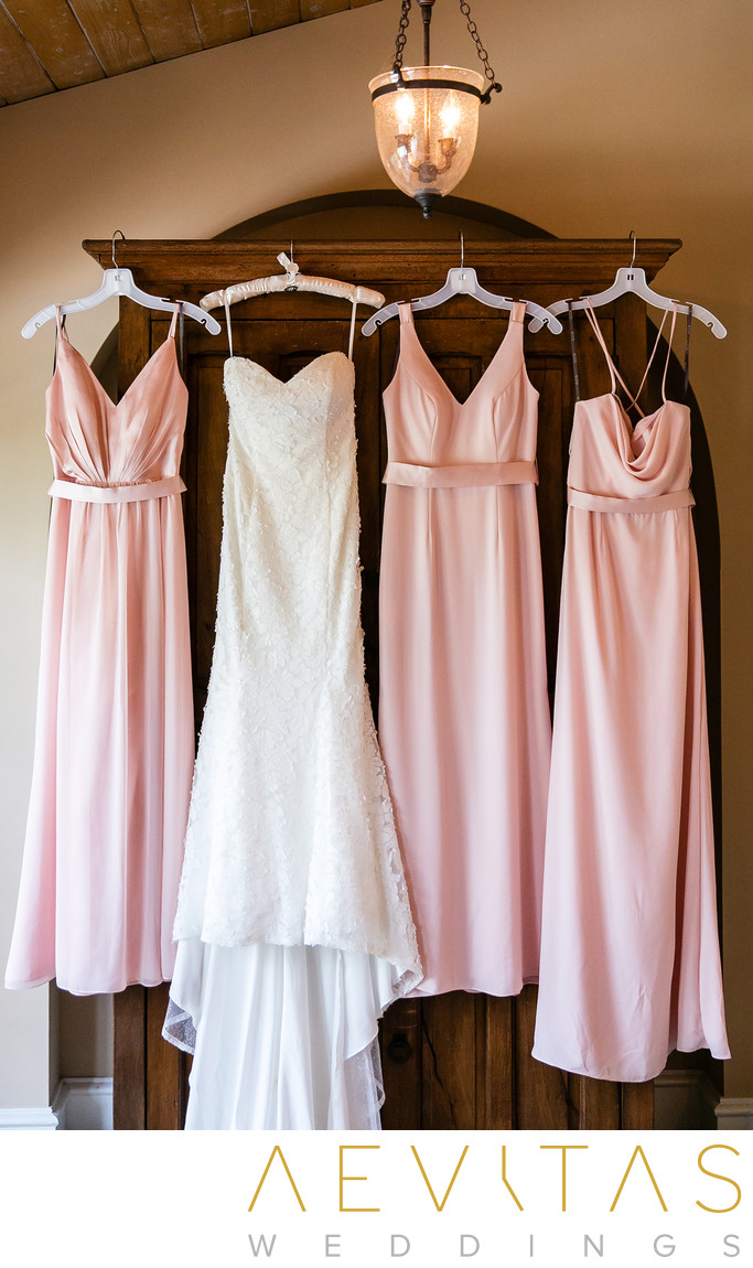 Wedding dress and bridesmaids pink dresses hanging