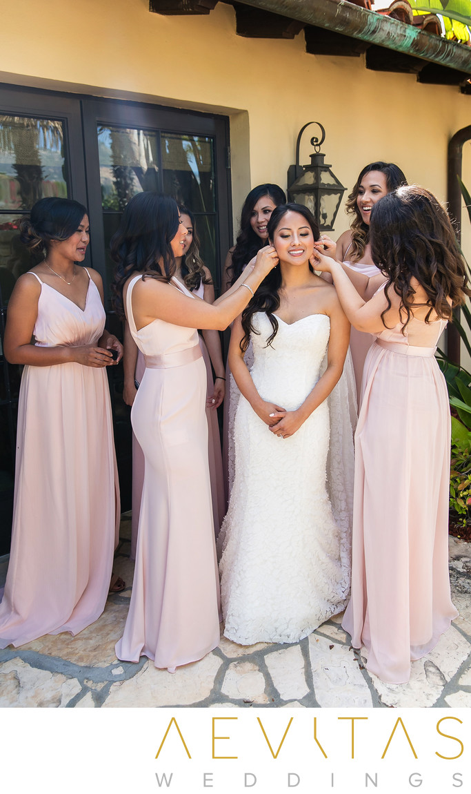 Bridesmaids helping bride with earrings outside cottage
