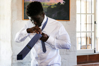 Groom fixing tie at Santa Barbara Historical Museum