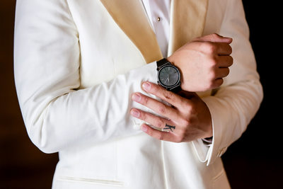 Close-up shot of groom's watch and engagement ring