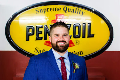 Groom portrait in front of a vintage Pennzoil sign