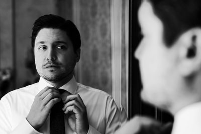 Reflective groom getting ready photo in black and white