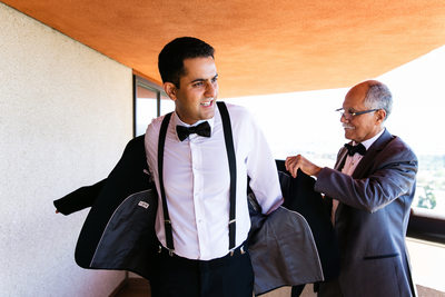 Groom putting on suit jacket with father Hotel Irvine