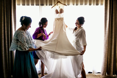 Bride, mom and sister admiring dress at Hotel Irvine