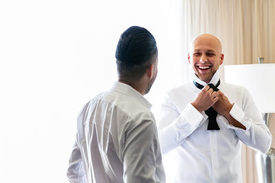Groom tying bowtie with best man at Sacramento hotel