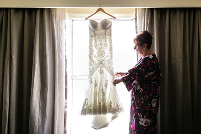 Mom admiring wedding dress in Los Angeles hotel suite