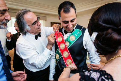 Parents tie sashes on groom at Armenian wedding