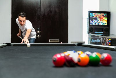Groom playing pool by Los Angeles wedding photographer