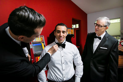 Groom fixing groomsman's bowtie at Los Angeles wedding