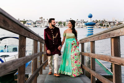 Indian couple walk along wooden jetty in Newport Beach
