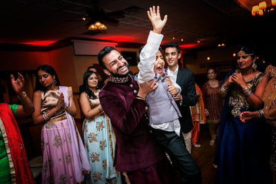 Groom lifts young boy at Indian Sangeet party