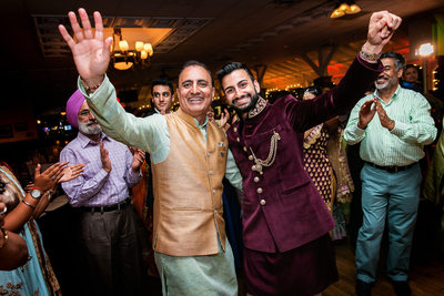 Groom and father dancing at Indian Sangeet ceremony