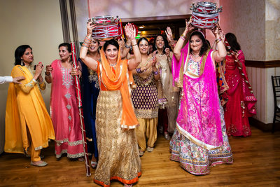 Women carrying drums at Indian Sangeet ceremony