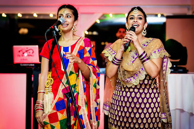 Women in saris singing at Indian Sangeet party