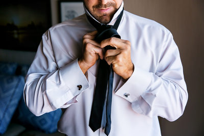 Candid photo of groom fixing tie in Santa Barbara