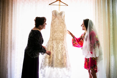 Bride and mom admire wedding dress in Santa Barbara