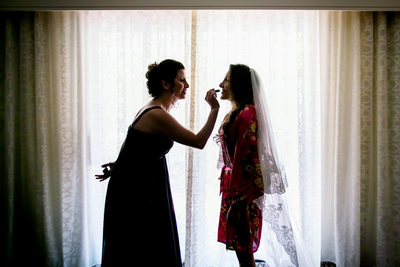 Bride having lipstick applied at hotel suite window