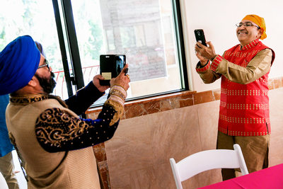 Family taking photos on cell phone at Sikh wedding