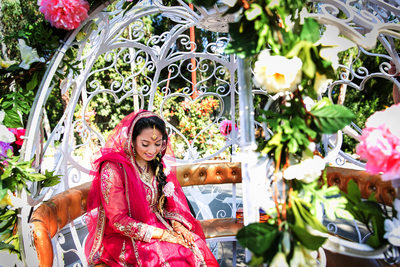Indian bride waiting in floral carriage in San Diego