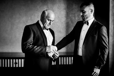 Black and white groom with father getting ready photo