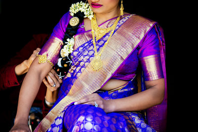 Bride in purple sari by Indian wedding photographer