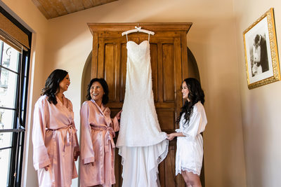 Bride, mom and sister admiring wedding dress in suite