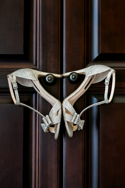 Bride's shoes on handles of wooden door in Sacramento