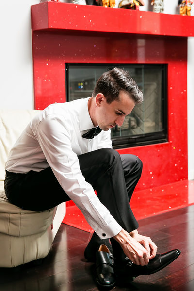 Groom tying shoes with red fireplace in Los Angeles
