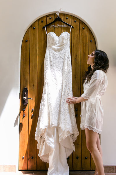 Bride admires wedding dress with arched wooden door