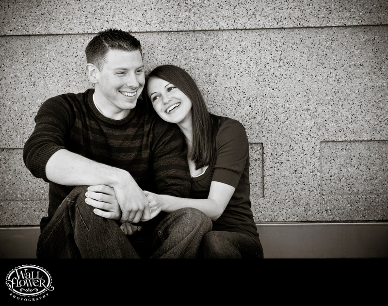 Engagement portrait sitting against concrete wall