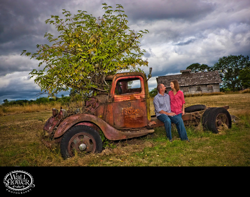 Engagement portrait by rusty truck under cloudy skies