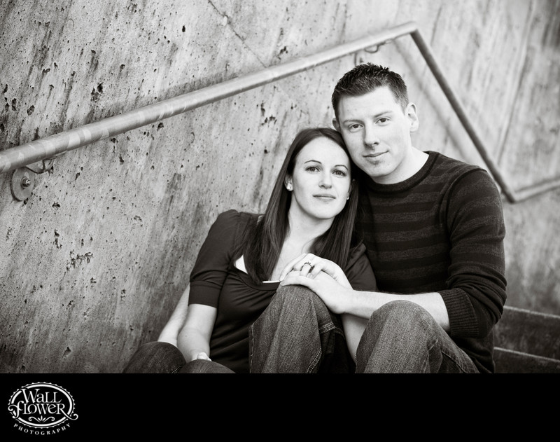 Engagement portrait on concrete steps with zig-zag rail