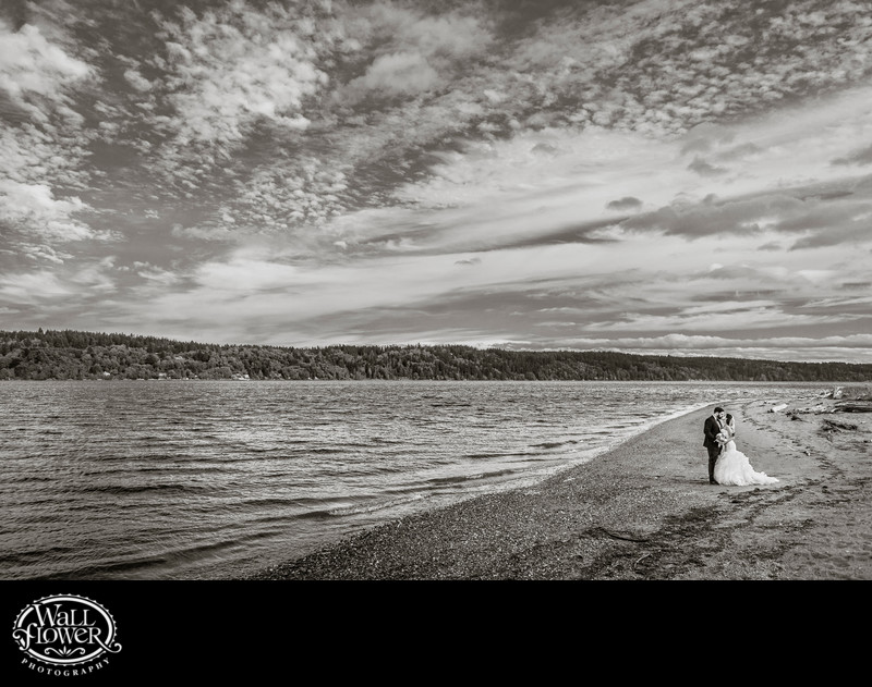 Bride and groom kiss on beach by Edgewater House