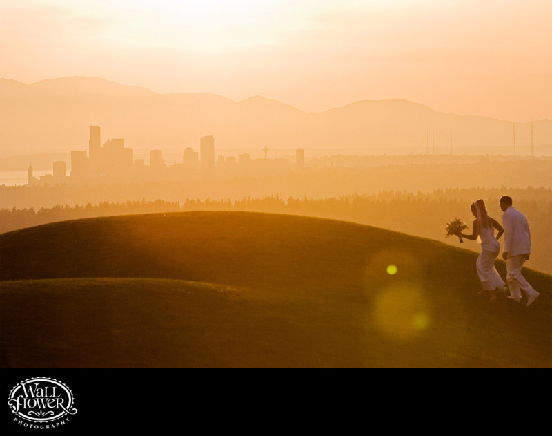 Bride and groom climb hill at Newcastle Golf Club to view of Seattle at sunset