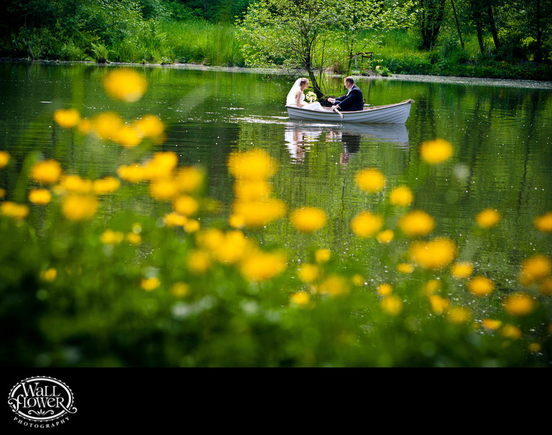Bride and groom in rowboat on Sanders Estate pond