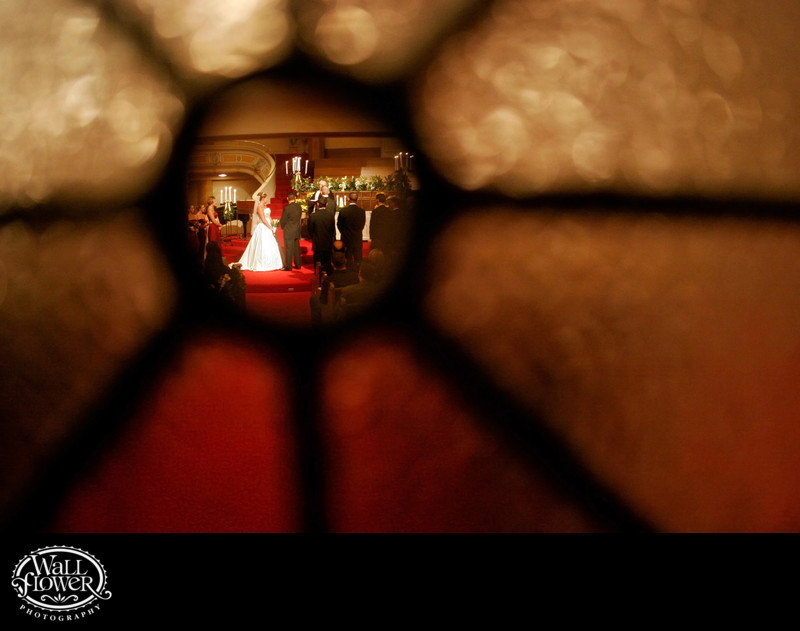 Wedding ceremony framed by window in sanctuary door