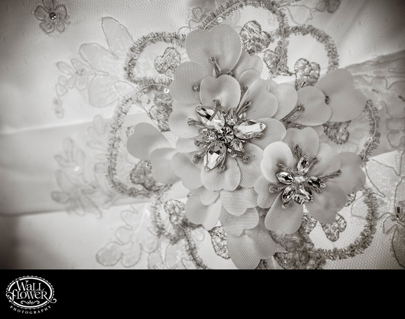 Detail of beading and fabric flowers on wedding dress