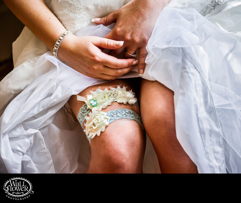 Detail of garters on bride's thigh with ring, bracelet