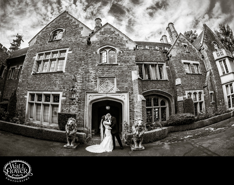 Fisheye portrait of kiss at Thornewood Castle entrance