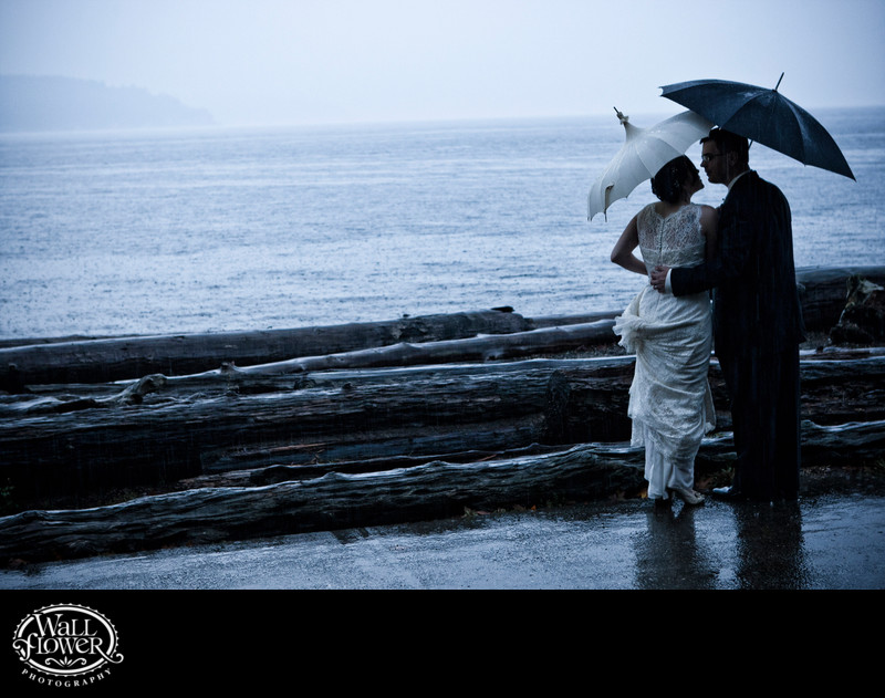 Bride and groom under umbrellas in rain at Owen Beach
