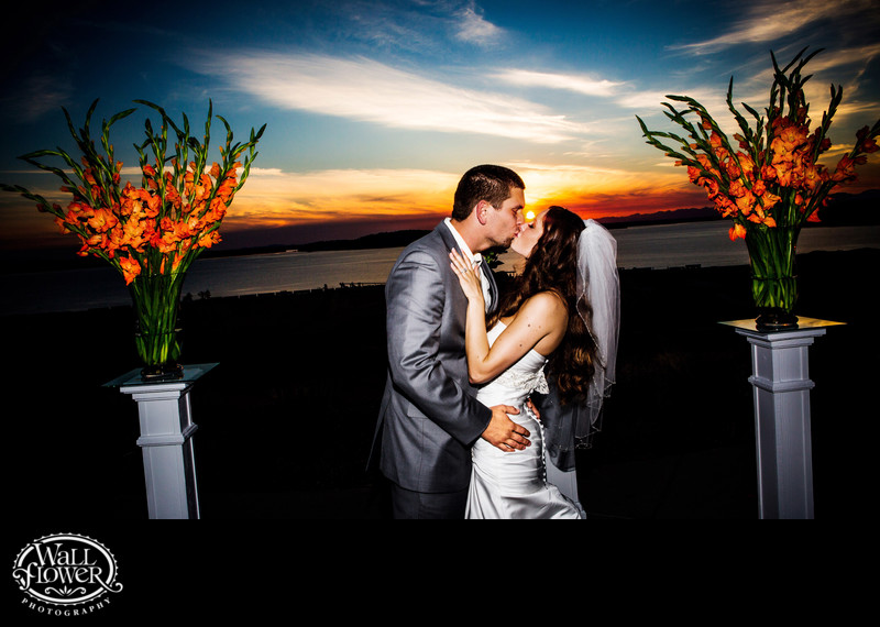 Bride and groom kiss on Chambers Bay patio at sunset