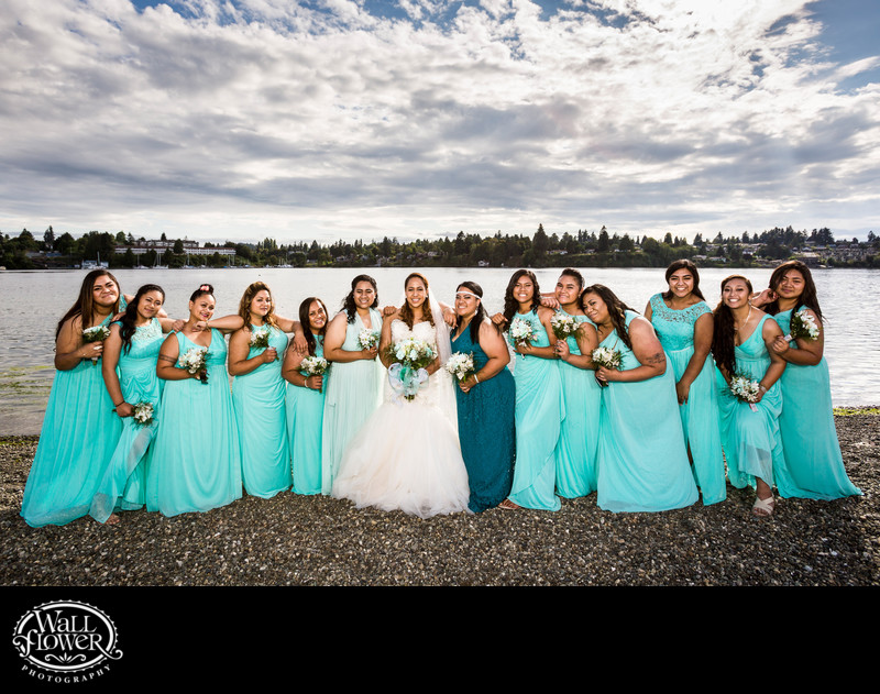 Bride and bridesmaids lean on each other on rocky beach